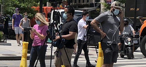 Reporters stand in a street with video and audio equipment