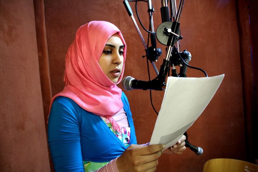 A young woman in a head scarf stands at a mic reading from a sheet of paper