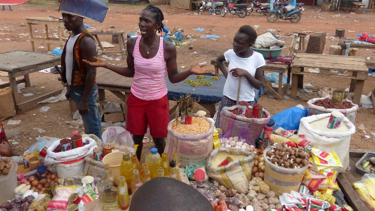 A woman and young girl stand by the food they are selling in a market