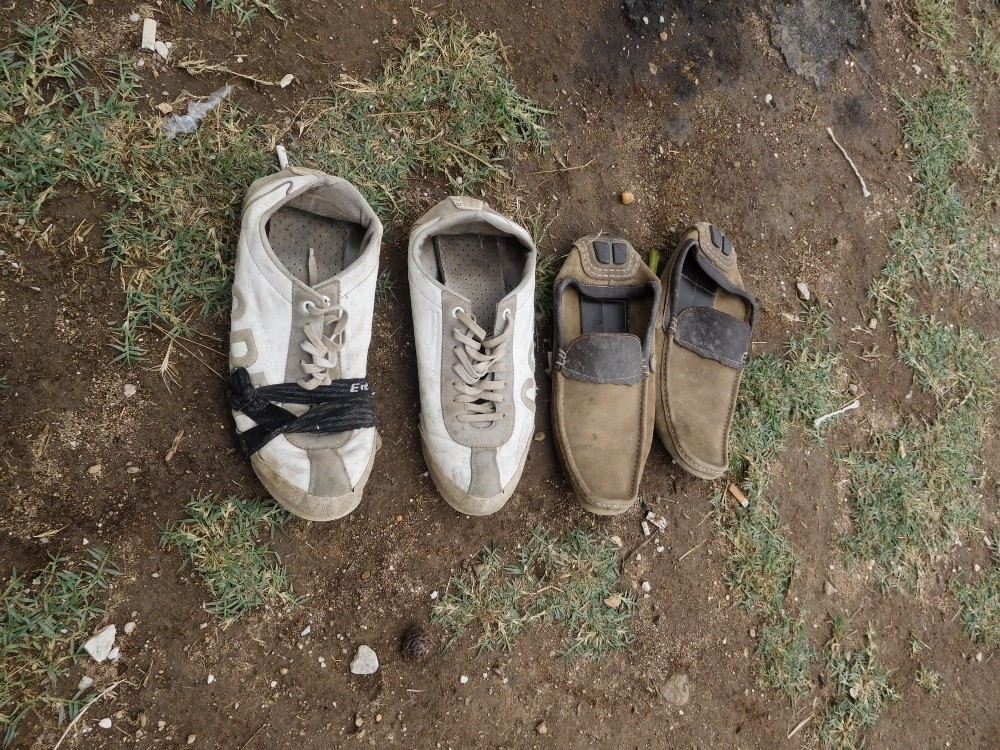 Two pairs of worn shoes are lined up on the ground
