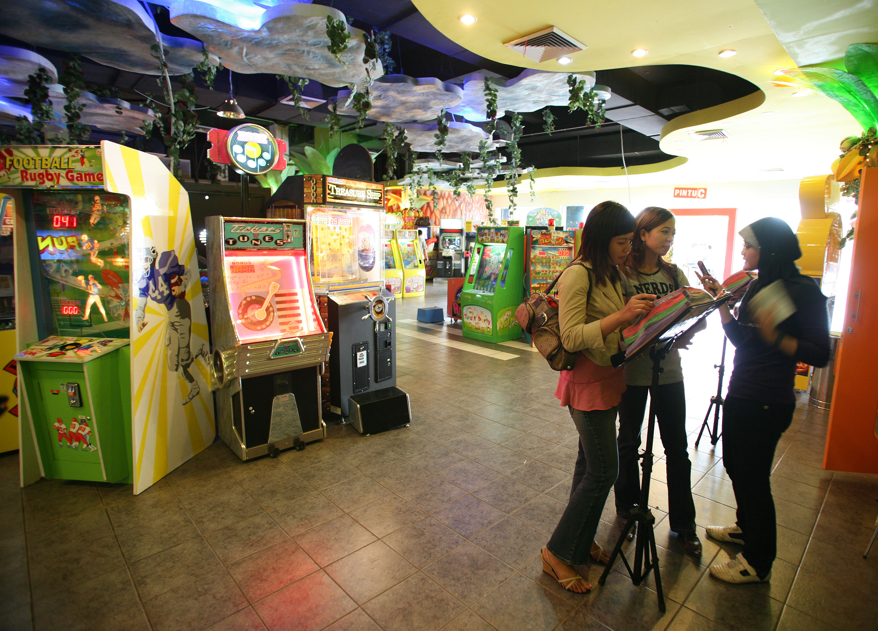 A journalist interviews two young women in an arcade.