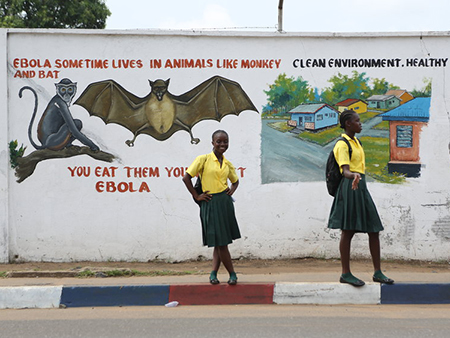 Two school girls stand in front of a mural about Ebola