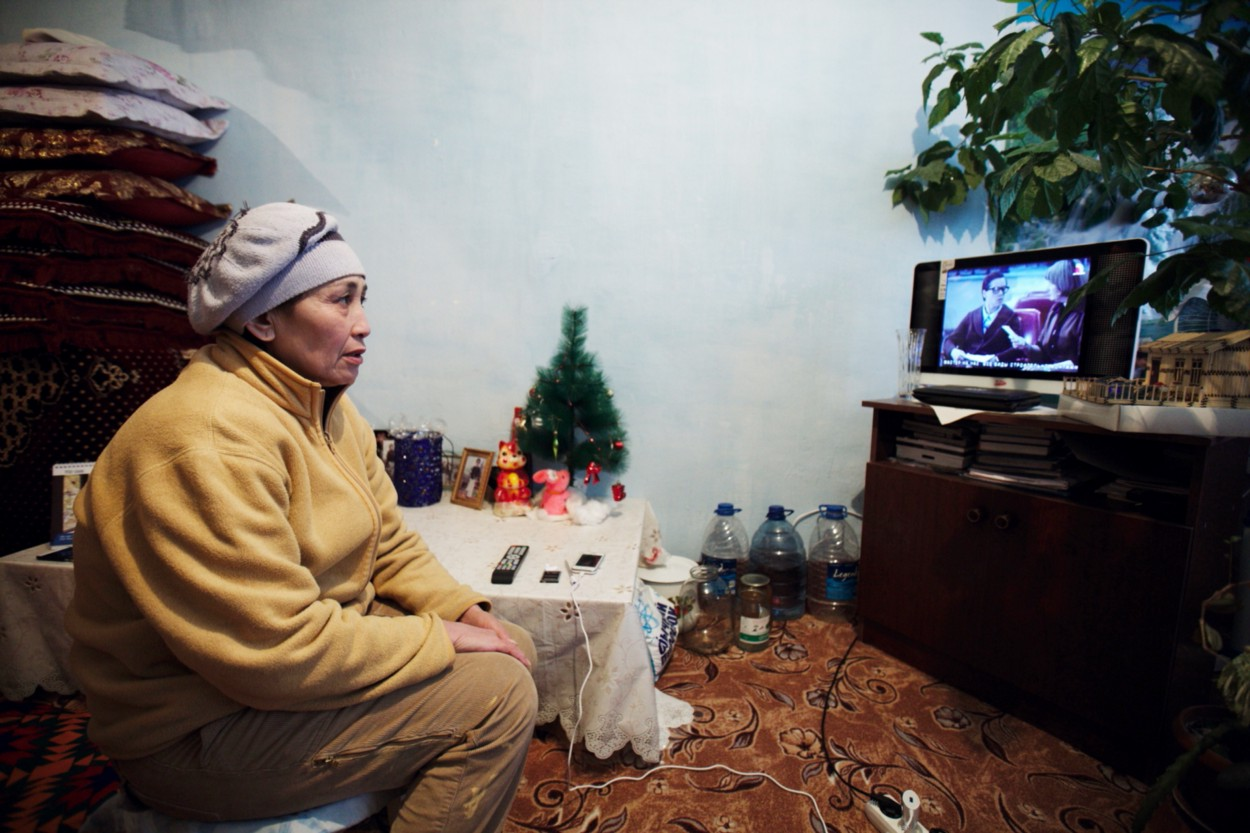 A woman sits in her living room watching TV.