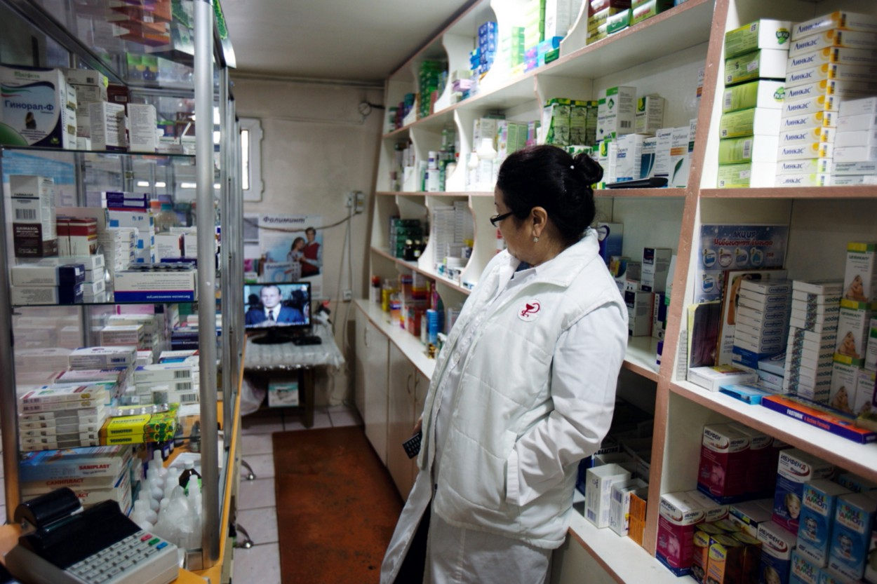 A woman in a white coat stands between two shelves of medications