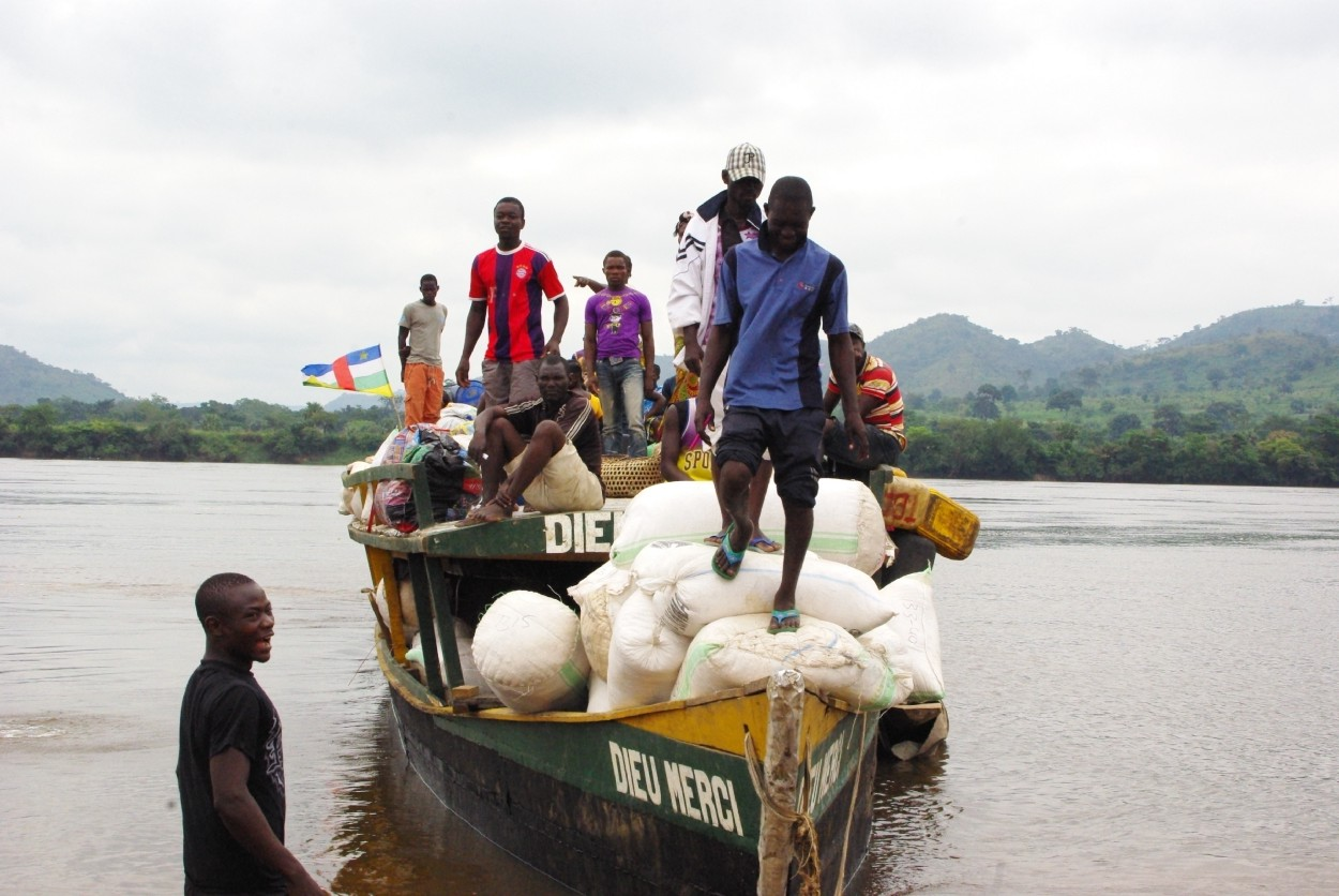 A man stands on a pile of filled sacks on the front of a boat