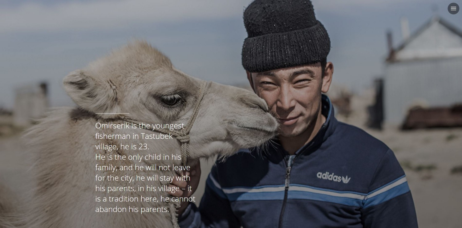 A young man stands next to a camel
