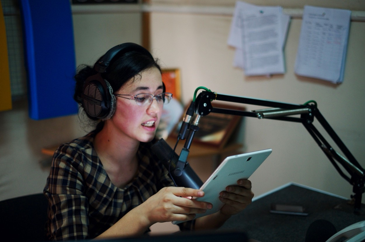 A woman wearing headphones sits at a mic reading from a tablet.