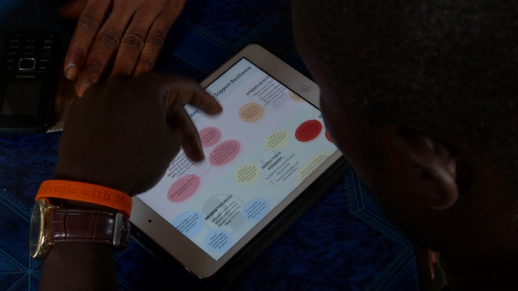 A man looks at the information ecosystem infographic on a tablet