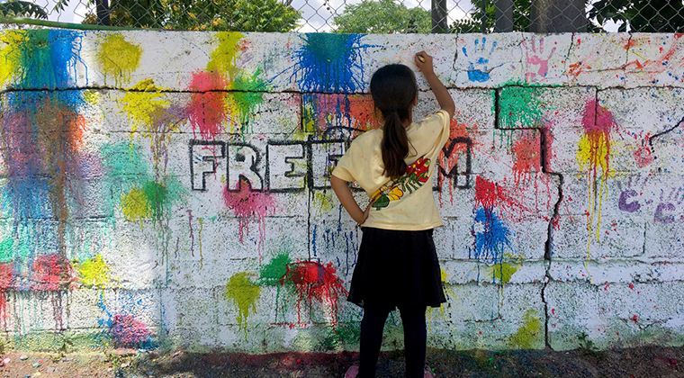 A girl writes on a brick wall that is covered in paint splatters
