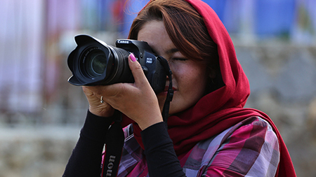An Afghan woman photographs