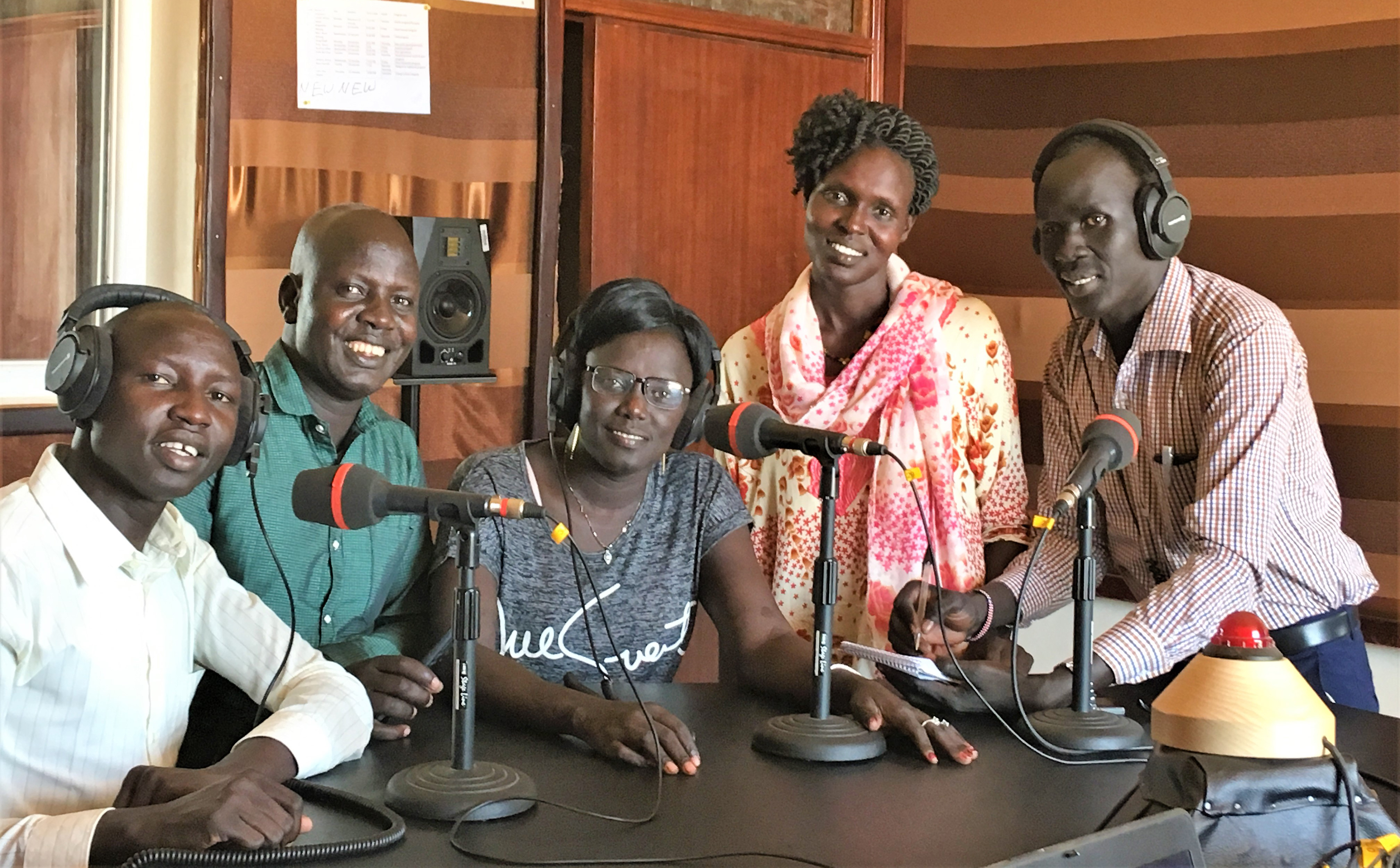 3 men and 2 women sit at a table in the Aweil radio studio.