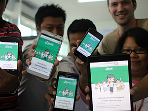 5 young people hold up their smart phones showing an app they designed.