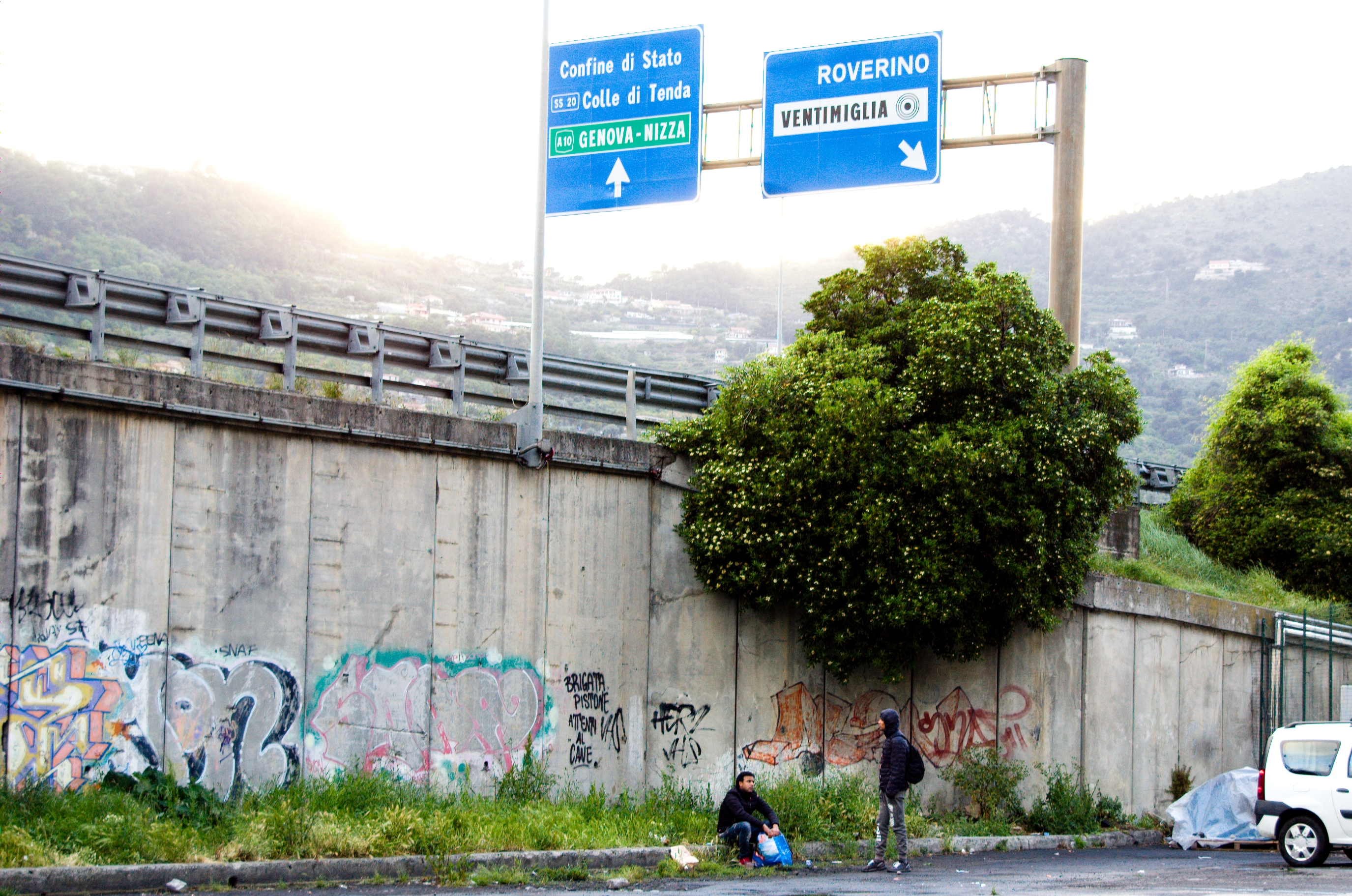 A wall on the side of a freeway is covered in graffiti