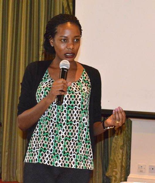 Dinah Kituyi speaking into a mic