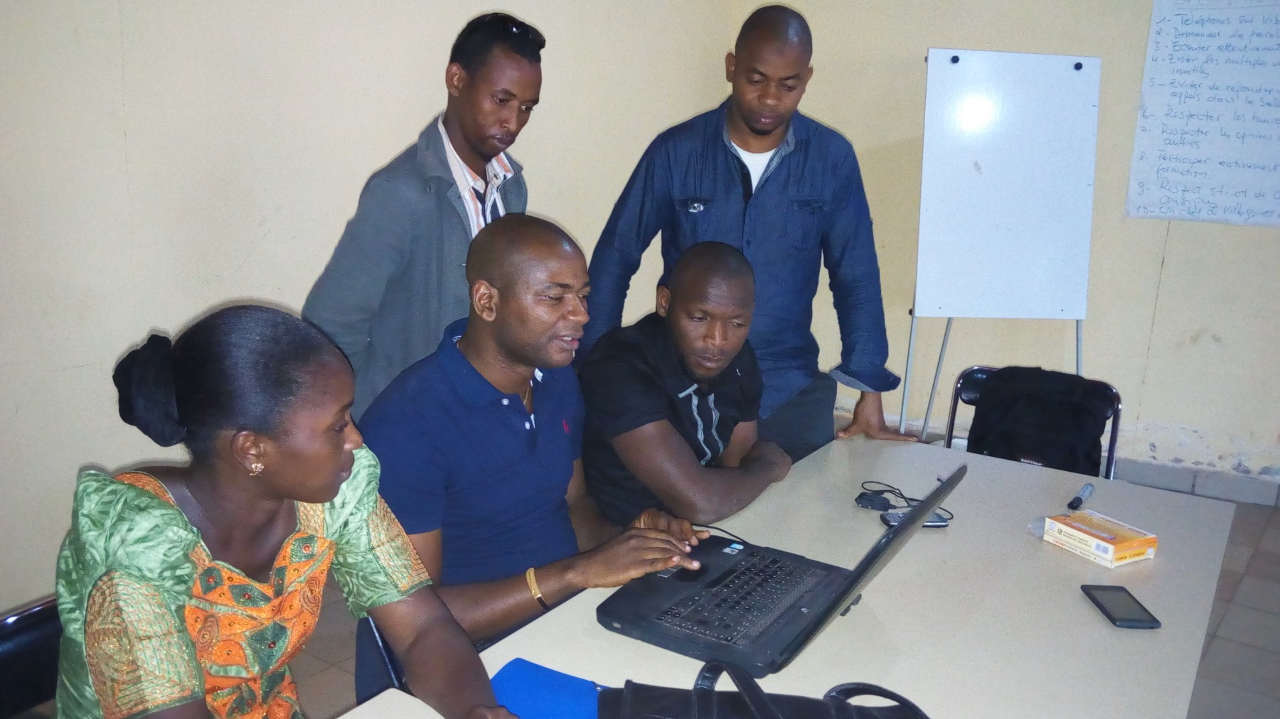 A trainer works with 4 journalists on a laptop computer