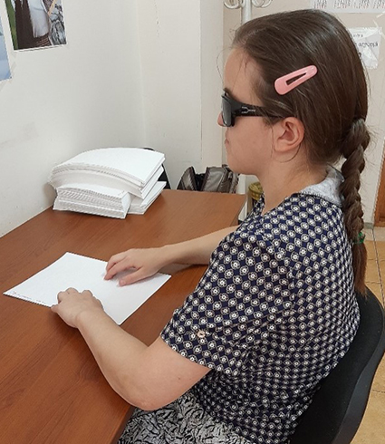 A woman wearing sunglasses sits at a table reading a Braille book