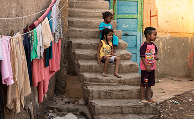 3 children on concrete steps, 2 sitting, 1 standing; clothes hang on a clothesline nearby