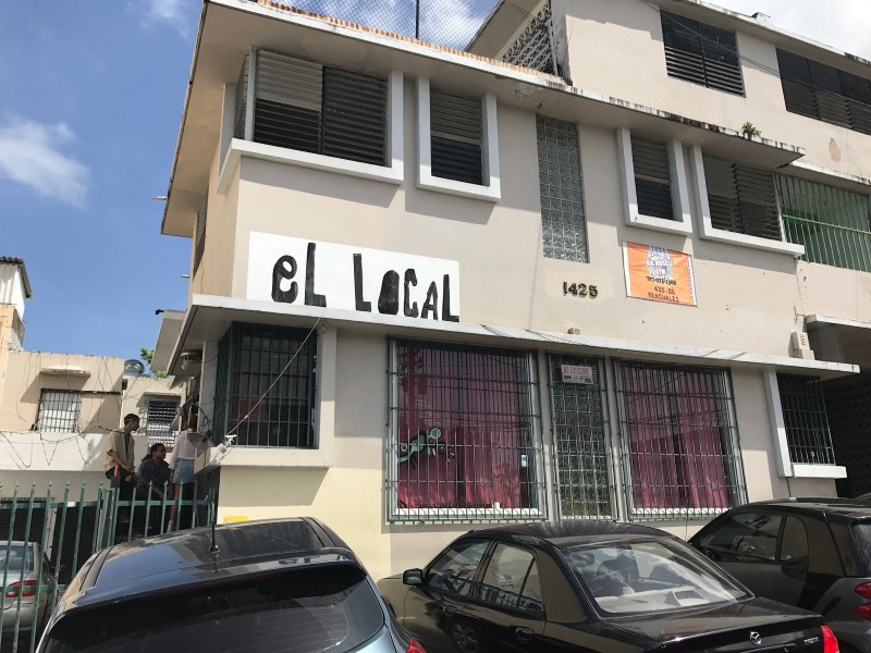 "A 3 story stucco building with the sign ""El Local"" on it."