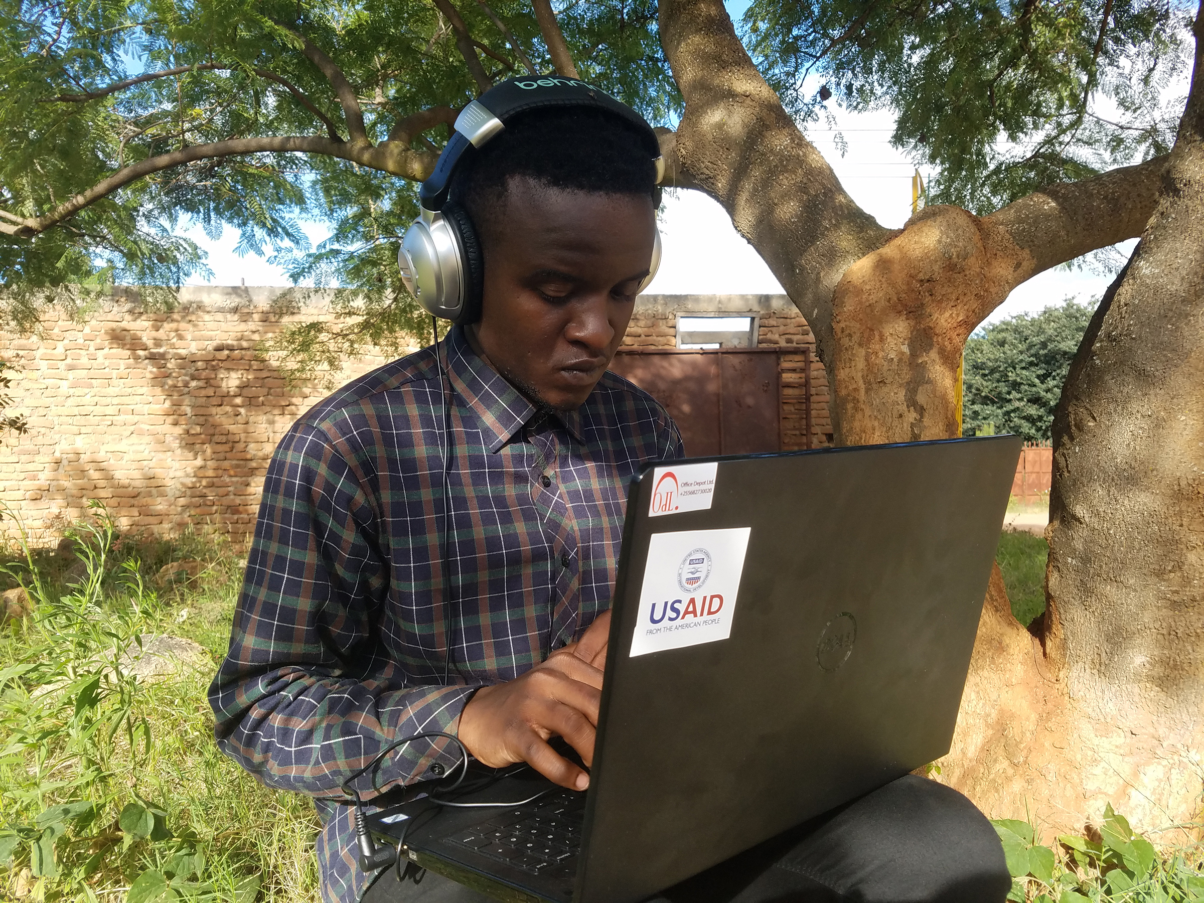 A man wearing headphones works on a laptop computer