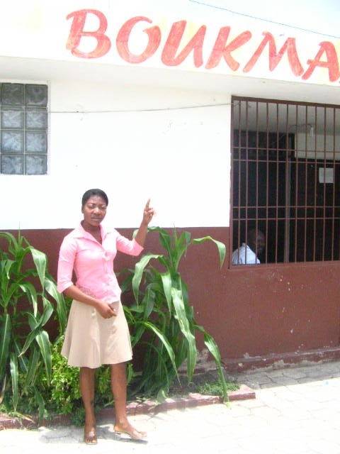 Fabienne pointing to a sign out front of the radio station where she works