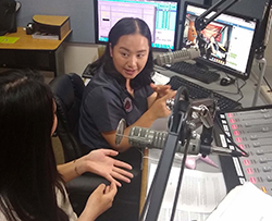 Two women sit talking in a radio studio