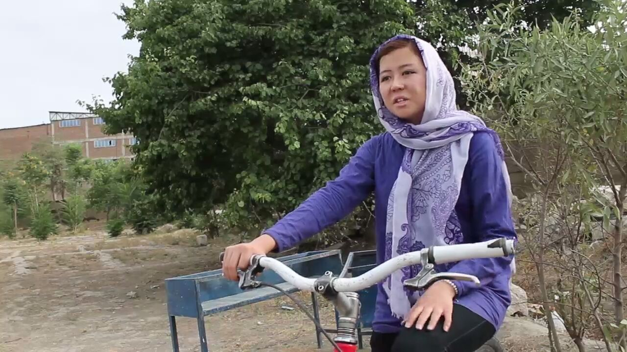 A young woman wearing a headscarf sits on her bike in a dirt area.