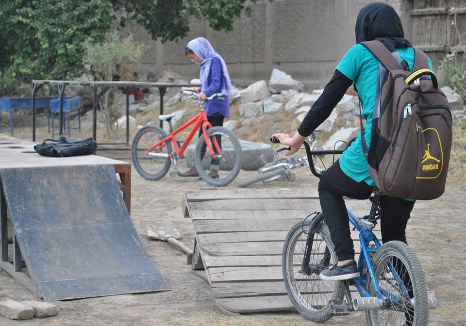 Two Afghan girls on bikes in a skateboard park.