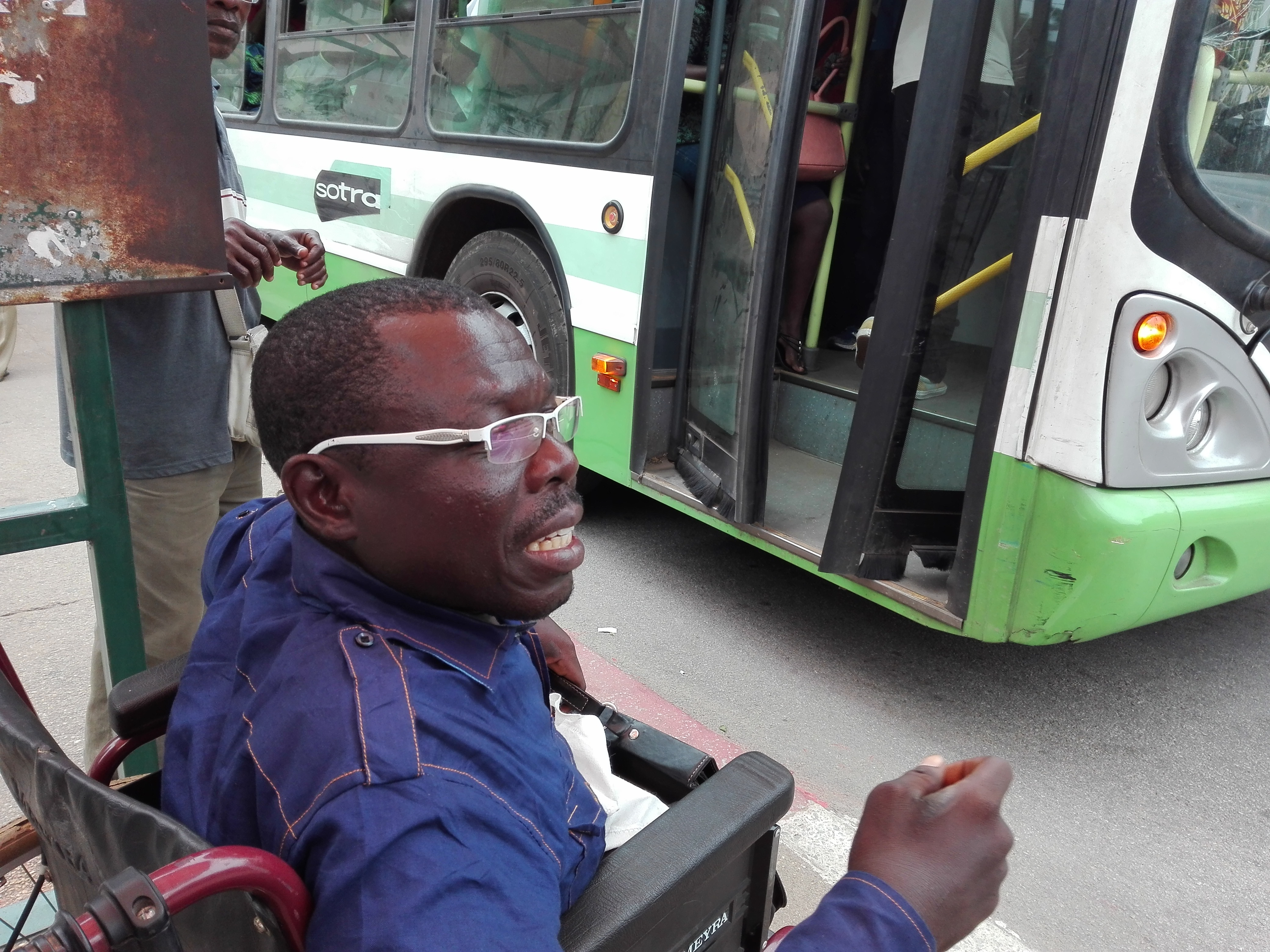 A man in a wheelchair waits on the side of the street where a bus has stopped.