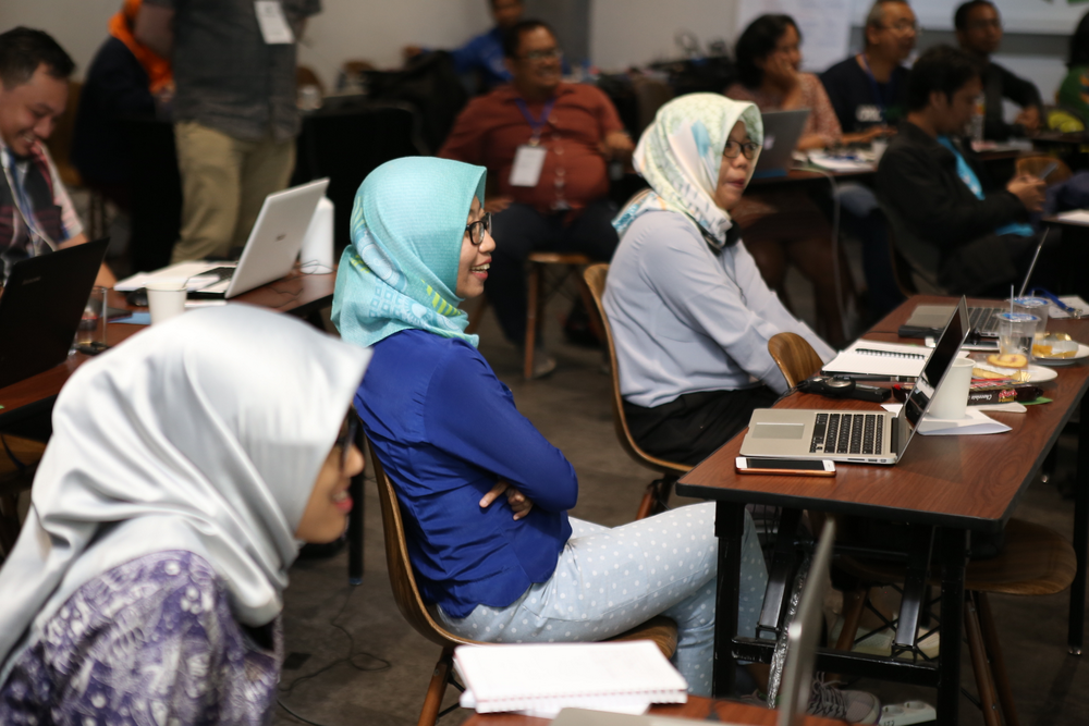 Three smiling women in headscarves sit at tables with laptops