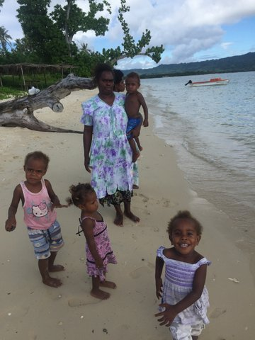 A woman stands with 4 children on the beach