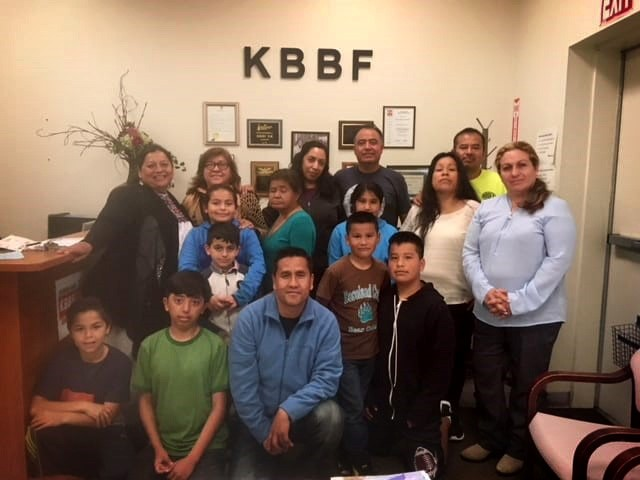 A group of people pose in front of a KBBF sign
