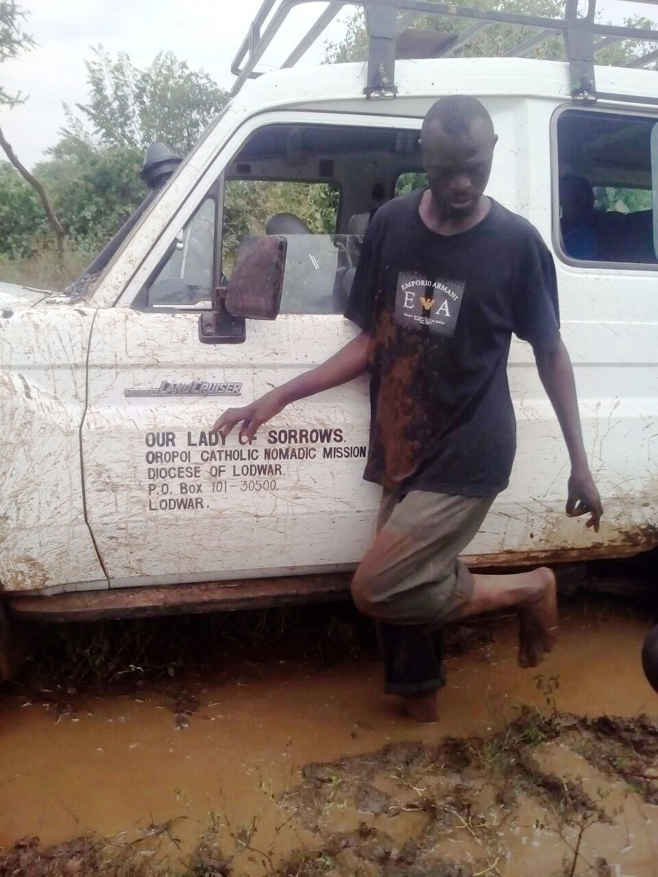 A man stands next to a truck that is stopped in muddy water