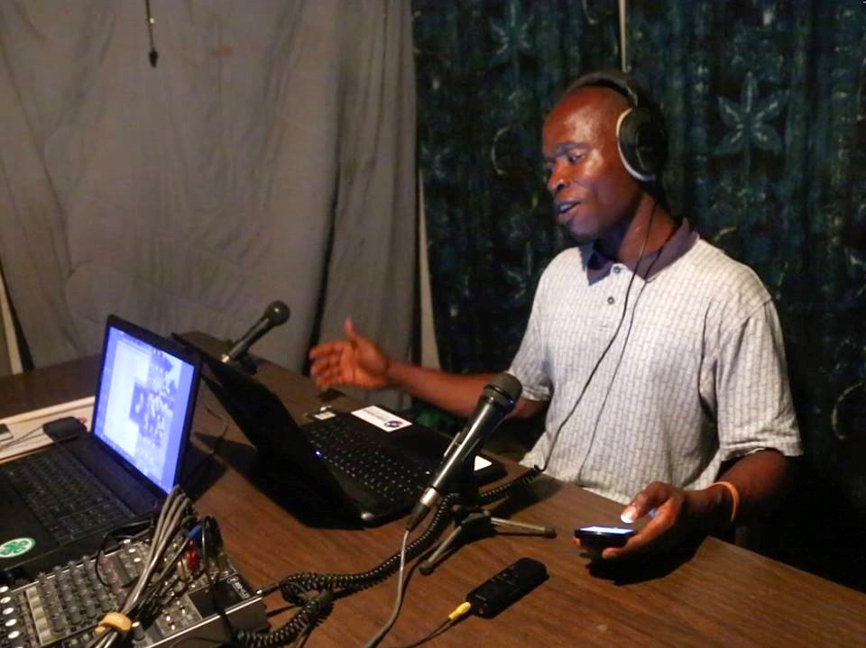 A man wearing headphones sits in front of a laptop and a microphone