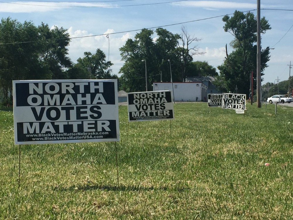 "A grassy area with signs posted: ""North Omaha Votes Matter"" and ""Black Votes Matter"""