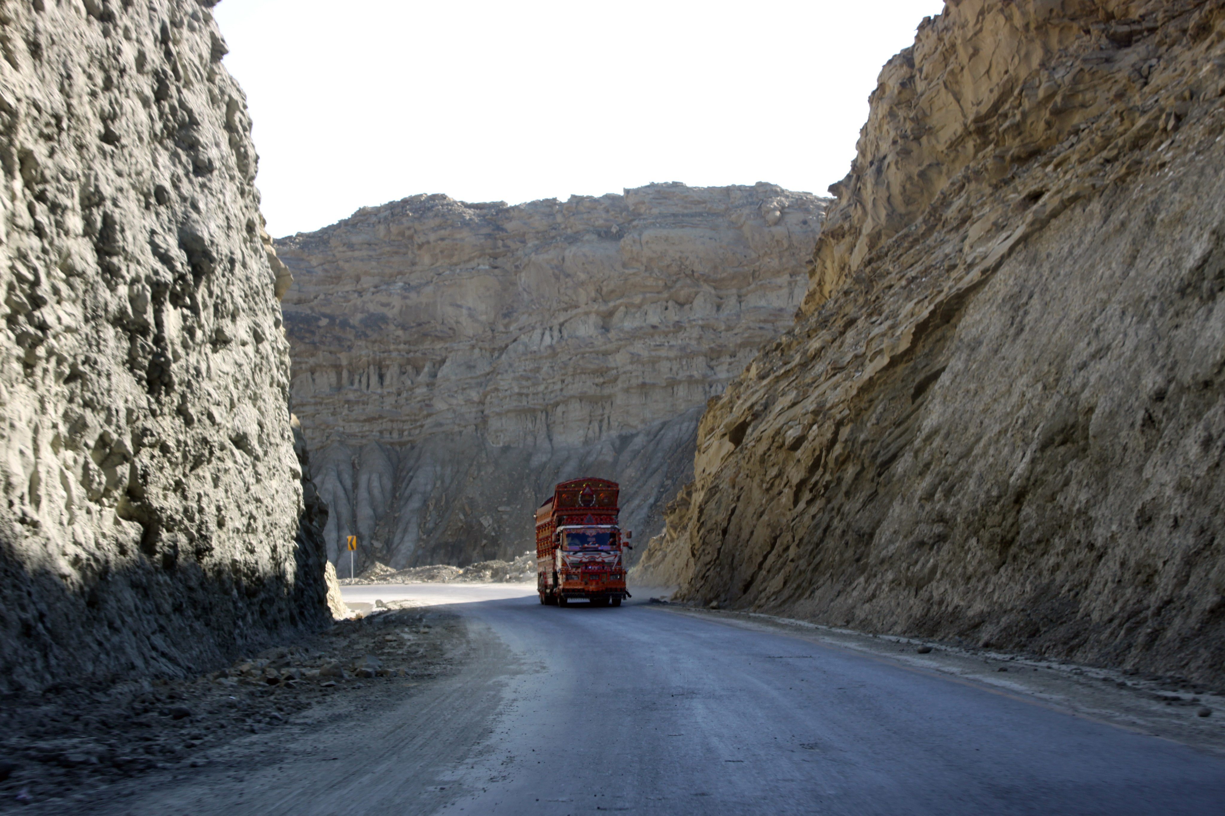 A truck travels on a highway with high cliffs on both sides.