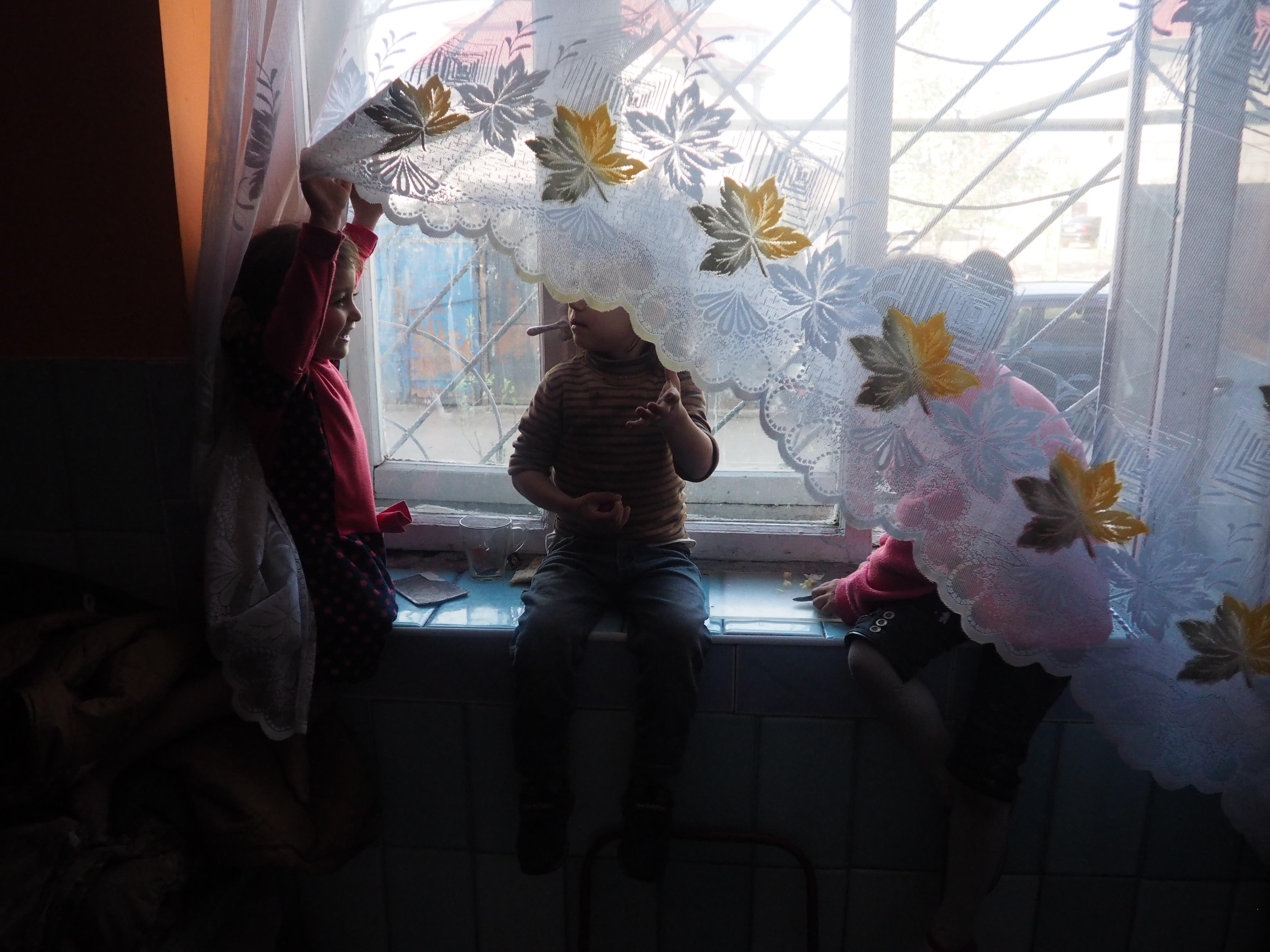 Three people look out a window with a flowered lace curtain.