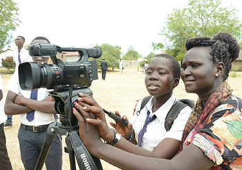 A woman and a student look through the viewer of a video camera