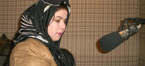 A woman sits in front of a mic in a radio studio
