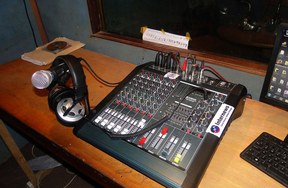 A mixing board, headphones and a mic sit on a weathered table in a radio studio