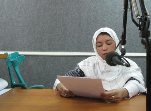 Amina sits at a microphone reading from a paper