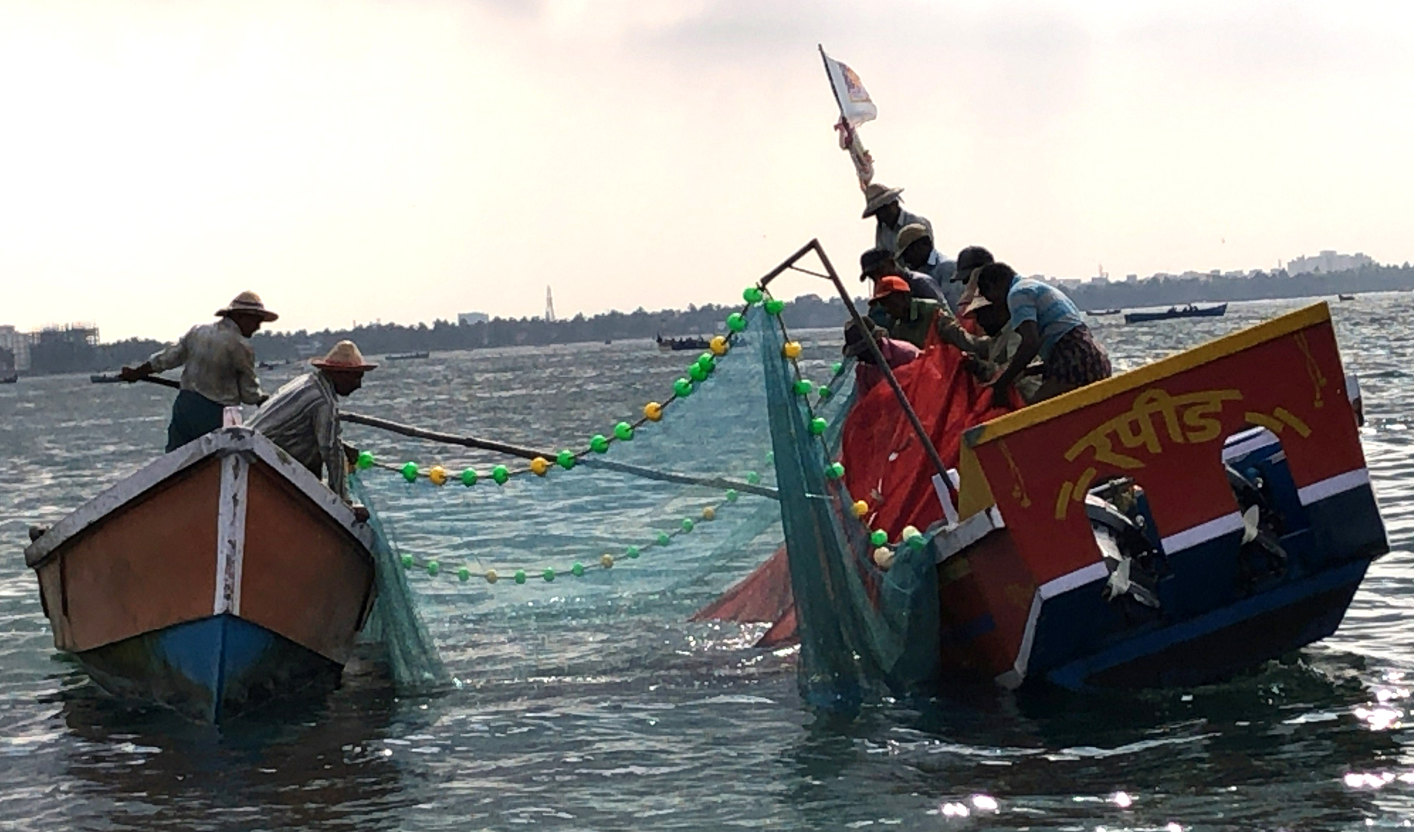 Two small boats are next to each other in the water, connected by ropes