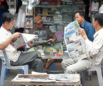 Three men sit around a table outside a newsstand reading newspapers.