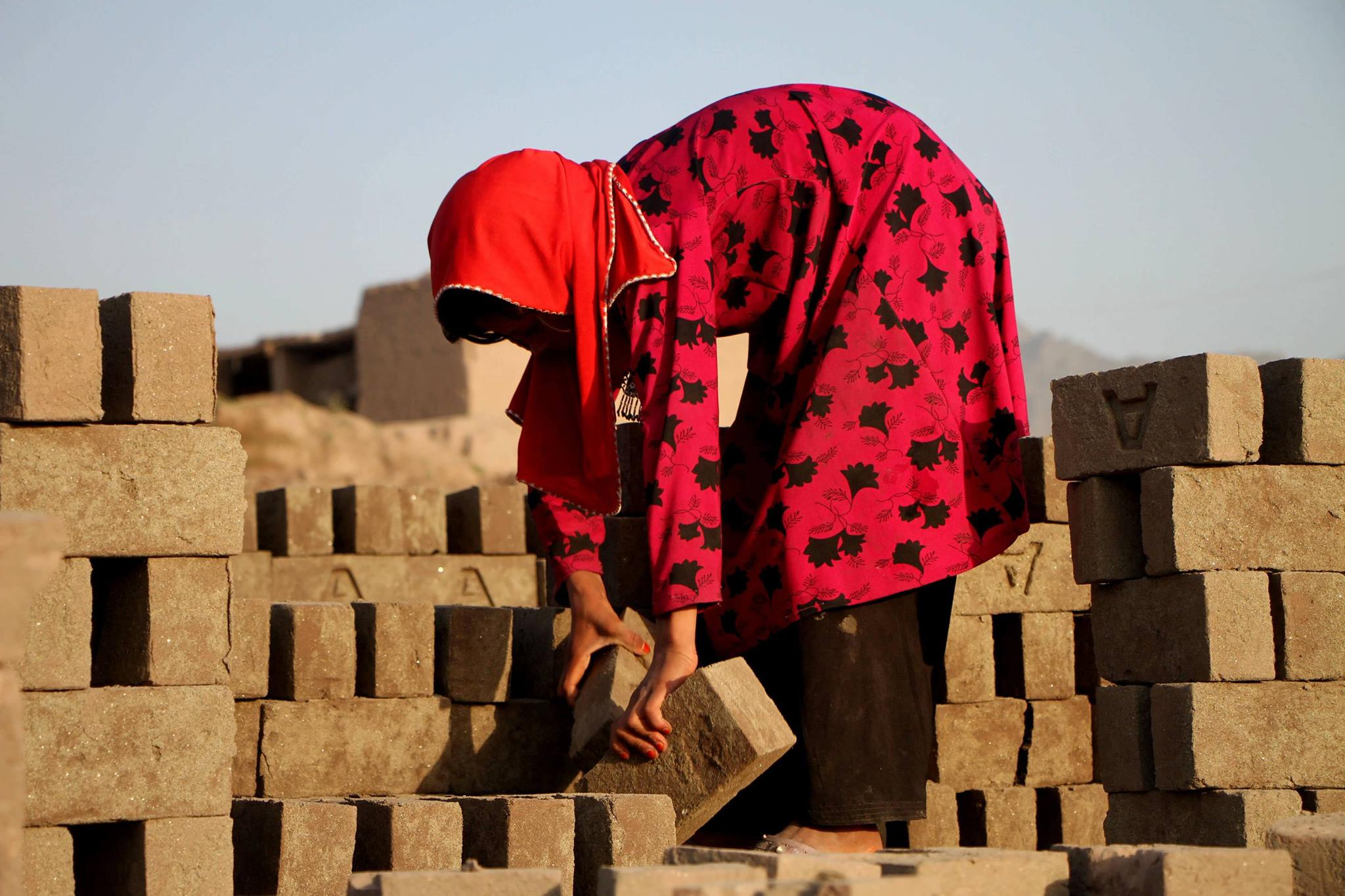 A young woman bends over picking up a mud brick.