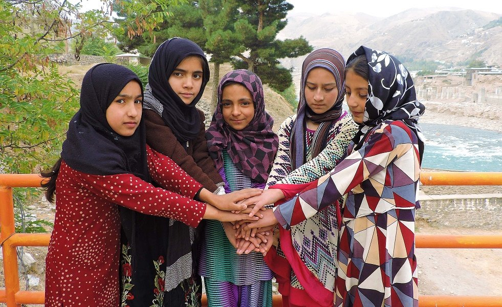 Five girls stand in a circle with their hands together, placed on top of each other.