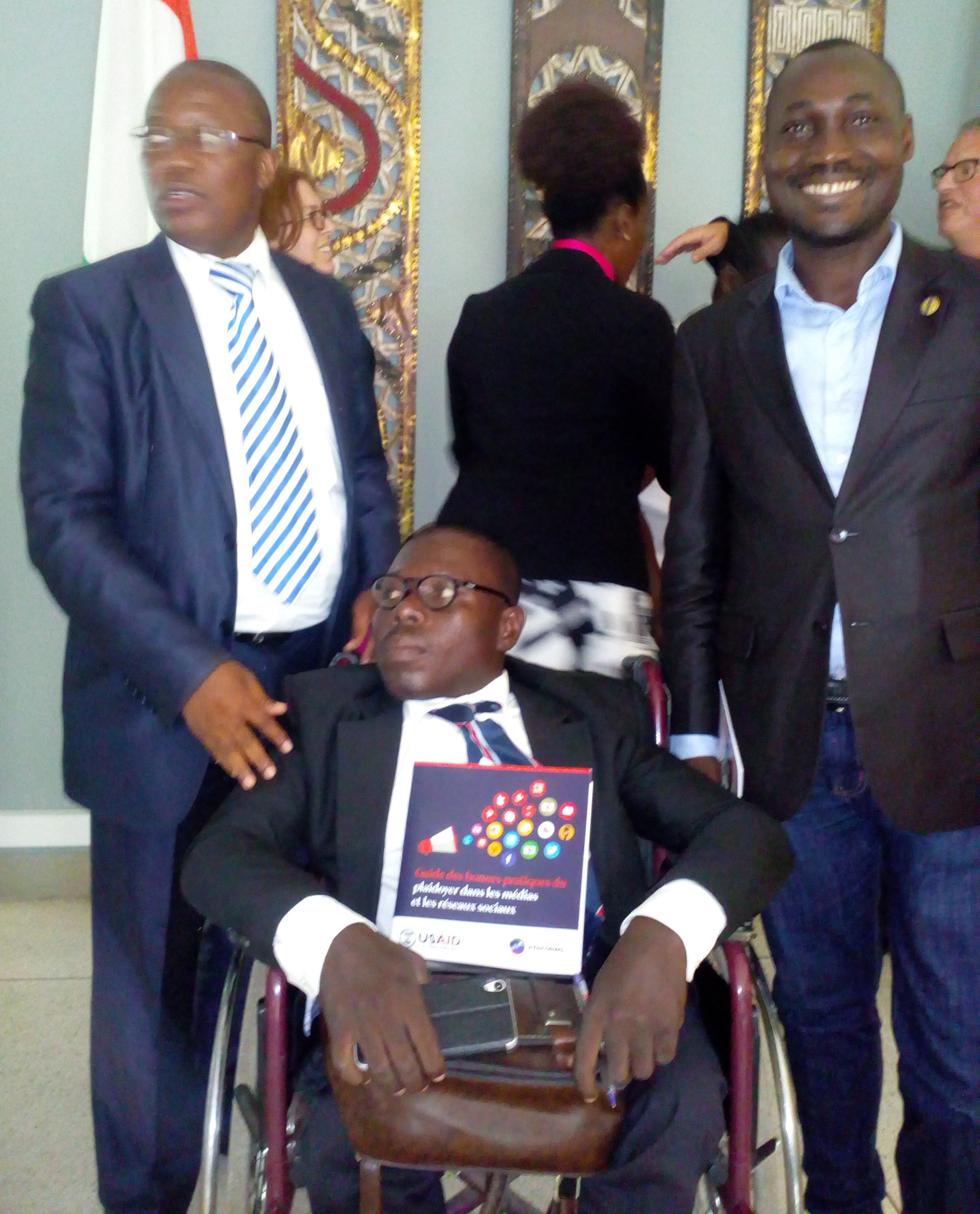 Two men stand next to a man in a wheelchair who is holding a book
