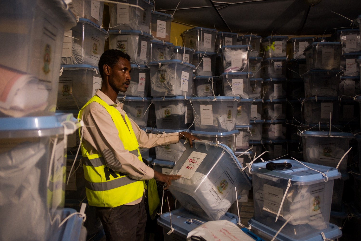 A man in a yellow vest looks at a plastic bin in a warehouse