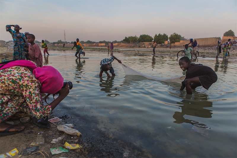 A woman photographs children playing with a net in a river