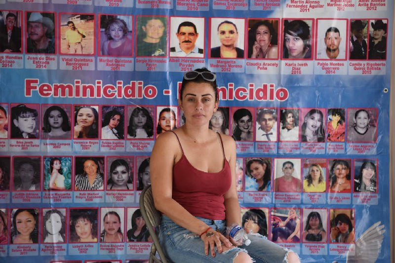 "A woman sits in front of a wall of photos of women with the title, ""Feminicidio"""