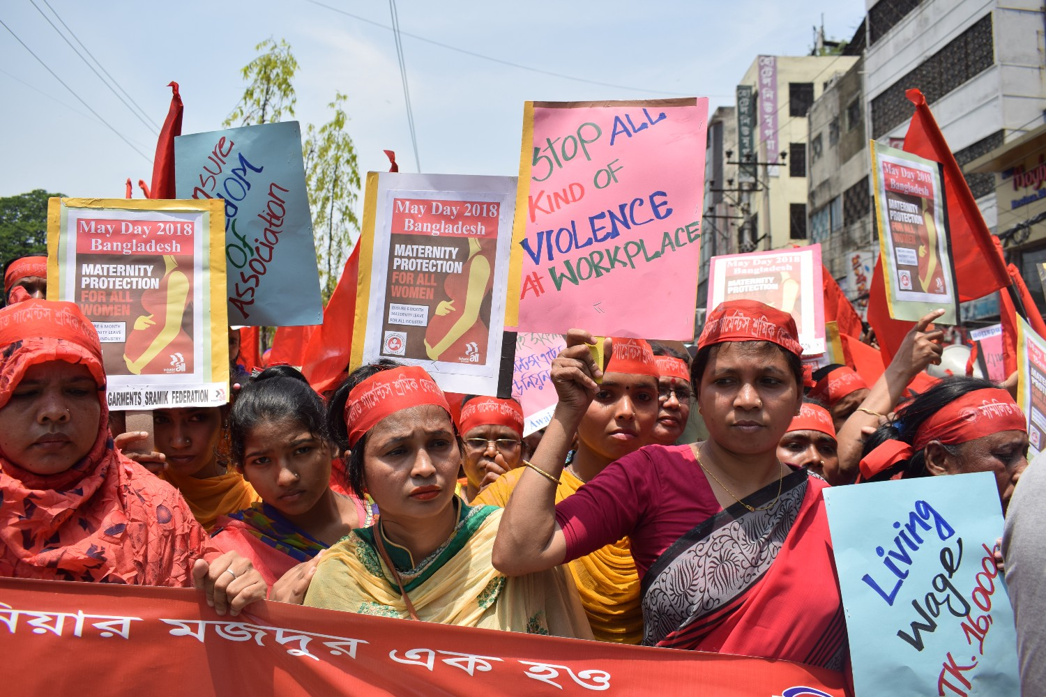 "Women dressed mostly in red participate in a protest carrying signs, ""Stop all kinds of violence at workplace"""