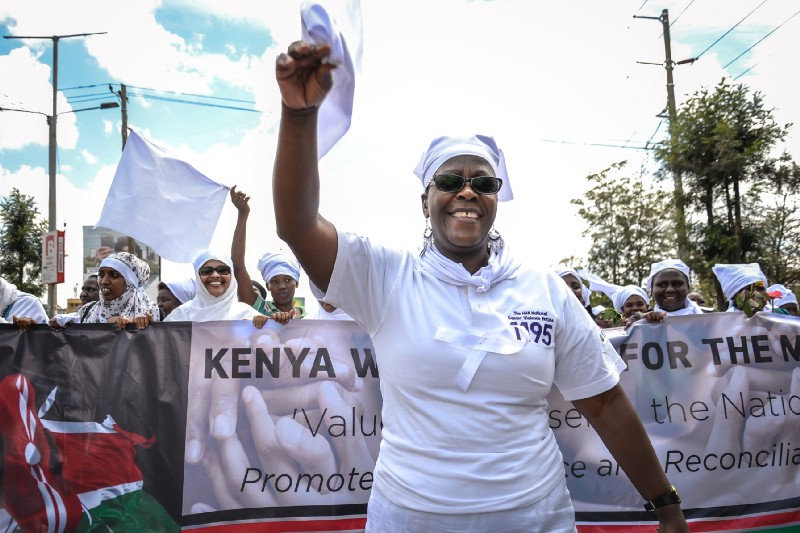 A woman dressed in white leads a protest; women in white march behind a banner.